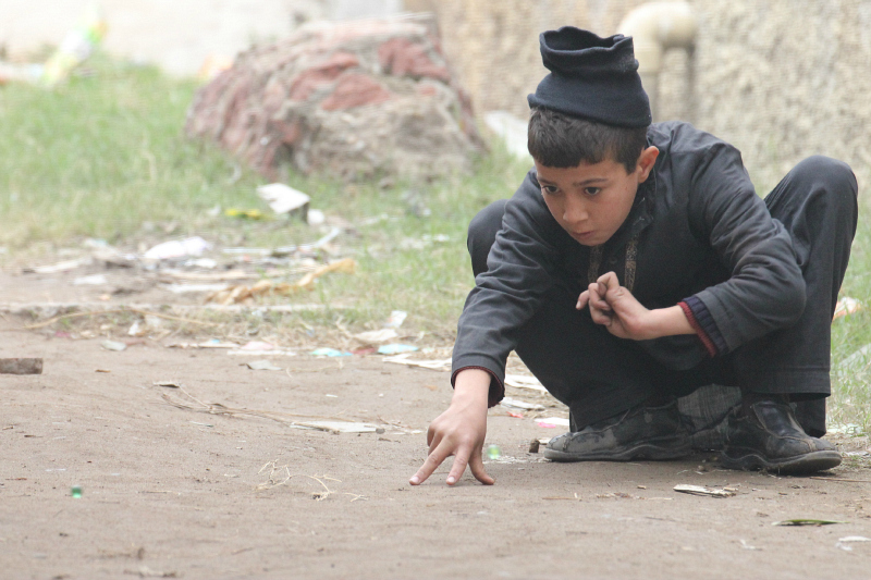 Kids playing marbles in a street
